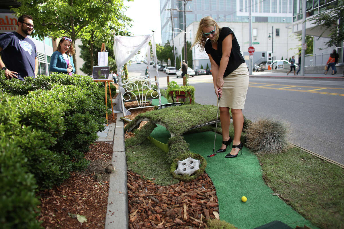 Erin Lodi hits a golf ball in the Weber Thompson and Briar Bates space in South Lake Union during PARK(ing) Day on Friday, Sept. 20, 2013. PARK(ing) Day is an event where businesses, community groups and individuals turn parking spaces into pop-up mini parks. There were about 40 of the parks across Seattle on Friday.