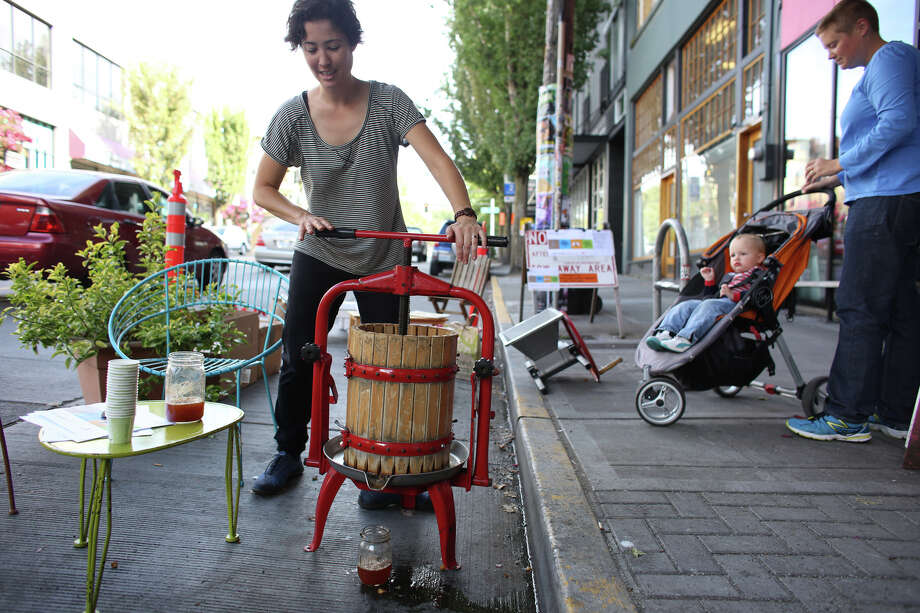 Whitney Fraser uses a cider press in the Capitol Hill EcoDistrict space during PARK(ing) Day on Pike Street in Capitol Hill. Photo: JOSHUA TRUJILLO, SEATTLEPI.COM / SEATTLEPI.COM