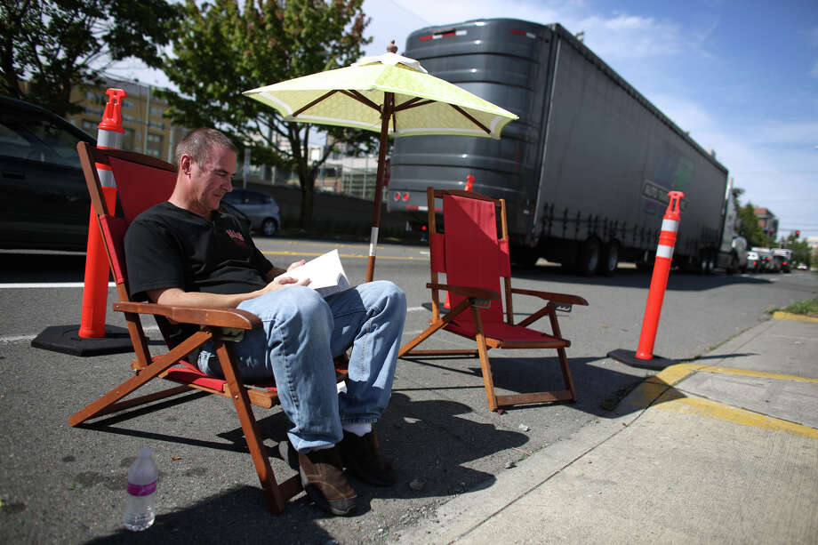 Seattle Academy of Arts and Sciences teacher Tom Hajduk sits in a chair in the school's space on 12th Avenue during PARK(ing) Day. Photo: JOSHUA TRUJILLO, SEATTLEPI.COM / SEATTLEPI.COM