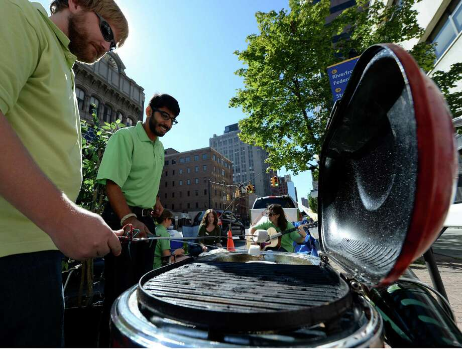 Drew Pollak-Bruce, left and Rohan Parikh heat up some marsh mellows in one of the parking spaces that were reserved today Sept 20, 2013 on Park(ing) Day in Albany, N.Y.  Park(ing) Day was initiated by Parks&Trails New York to make the public aware, protect and promote a network of parks, trails and open spaces throughout the state for the use and enjoyment by all.   (Skip Dickstein / Times Union) Photo: Skip Dickstein