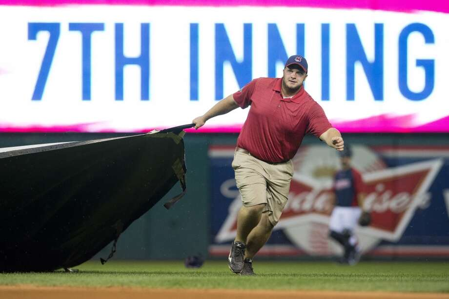 A member of the Indians grounds crew pulls out the tarp during a weather delay. Photo: Jason Miller, Getty Images