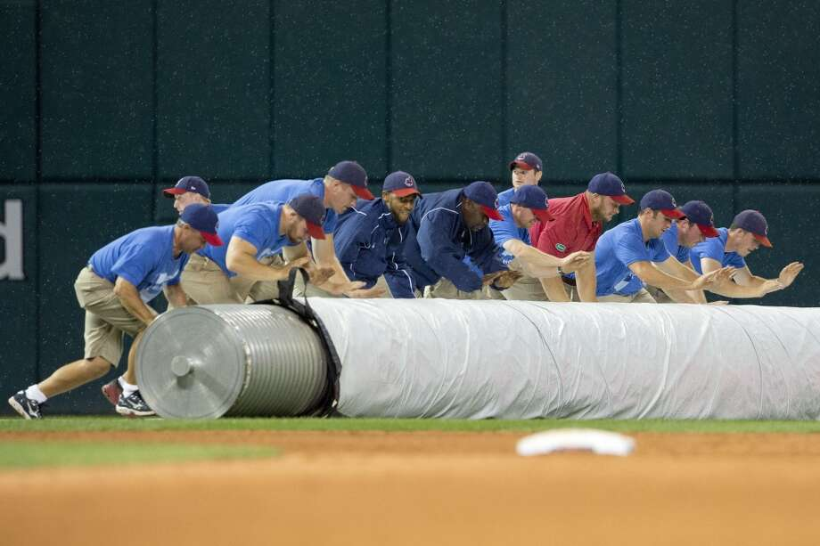 Members of the grounds crew roll out the tarp during the beginning of a weather delay. Photo: Jason Miller, Getty Images