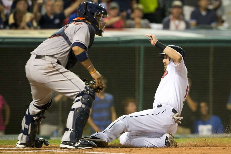 Catcher Carlos Corporan #22 of the Astros waits for the throw as Ryan Raburn #9 of the Indians slides into home. Photo: Jason Miller, Getty Images