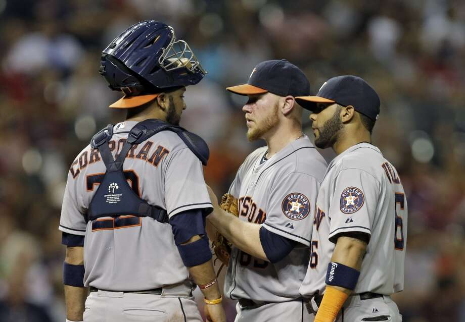 Astros starting pitcher Brett Oberholtzer, center, gets a visit from catcher Carlos Corporan, left, and shortstop Jonathan Villar. Photo: Mark Duncan, Associated Press