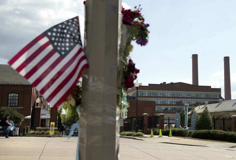 A makeshift memorial hangs on a lamppost across the street from the Washington Navy Yard four days after a gunman killed 12 people there. Photo: Carolyn Kaster / Associated Press