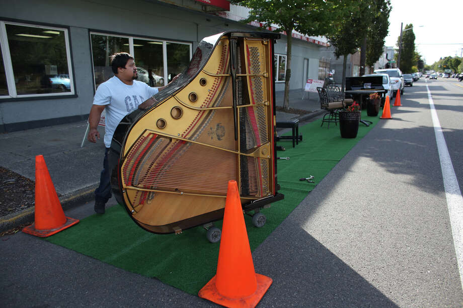 Piano movers maneuver a piano into the A-1 Piano Sales, Rentals Moving and Storage space  during PARK(ing) Day on Greenwood Avenue North. Photo: JOSHUA TRUJILLO, SEATTLEPI.COM / SEATTLEPI.COM