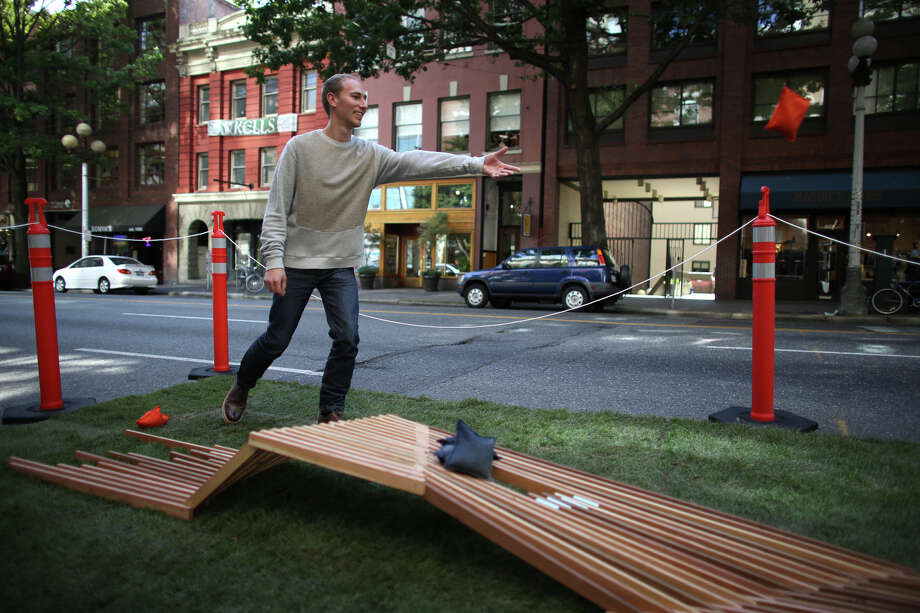 Adam Pazan tosses a bean bag in the Bohlin Cywinski Jackson Architecture space on 1st Avenue during PARK(ing) Day. Photo: JOSHUA TRUJILLO, SEATTLEPI.COM / SEATTLEPI.COM