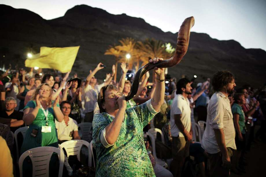 A woman blows a ram's horn Friday during a prayer of thousands of evangelical Christian pilgrims on the Dead Sea shore in the Judean Desert. Photo: Menahem Kahana / Getty Images