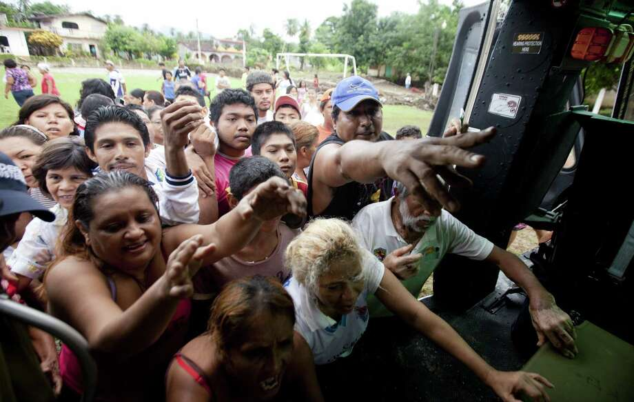 Villagers in San Jeronimo crowd around a helicopter from the Mexico attorney general's office to get aid Friday after the rains and floods caused by Tropical Storm Manuel. Photo: Associated Press