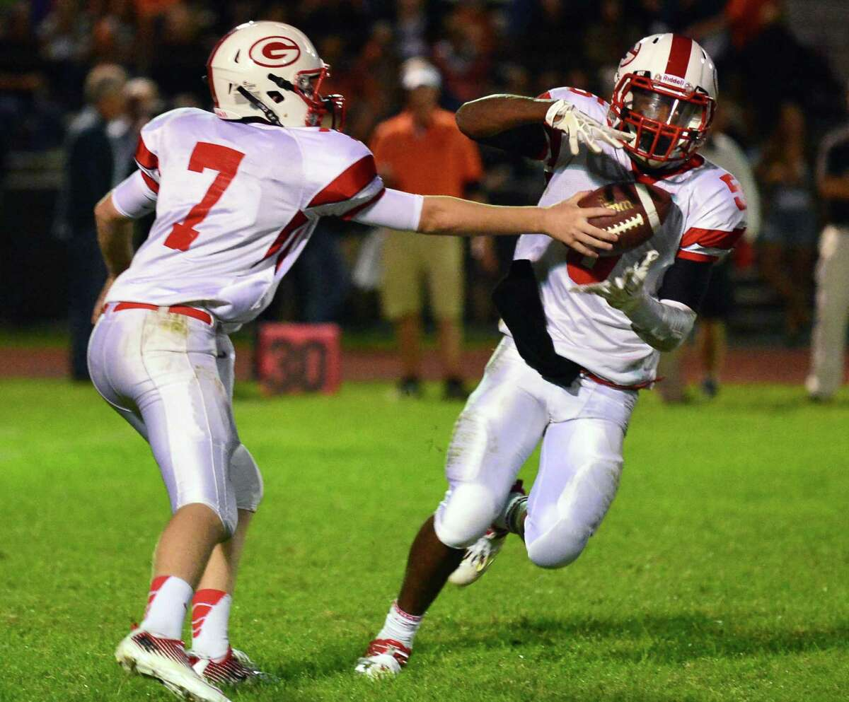 Guilderland QB #7 Frank Gallo, left, hands off to #5 Micaiah Henningham during Friday night's game against Bethlehem Sept. 20, 2013, in Delmar, NY. (John Carl D'Annibale / Times Union)