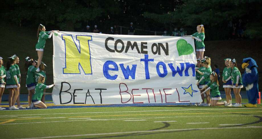 The Newtown Cheerleaders hold up a banner for the boys football team to run through as they come onto the field before their game against Bethel High School at Newtown High School, Newtown, Conn on Friday, September 20, 2013. Photo: H John Voorhees III