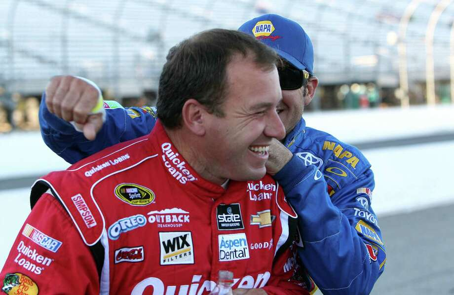 Ryan Newman finds himself on the receiving end of a surprise hug from Martin Truex Jr. after winning the pole position for Sunday's Sprint Cup race. Photo: Jim Cole, STF / AP