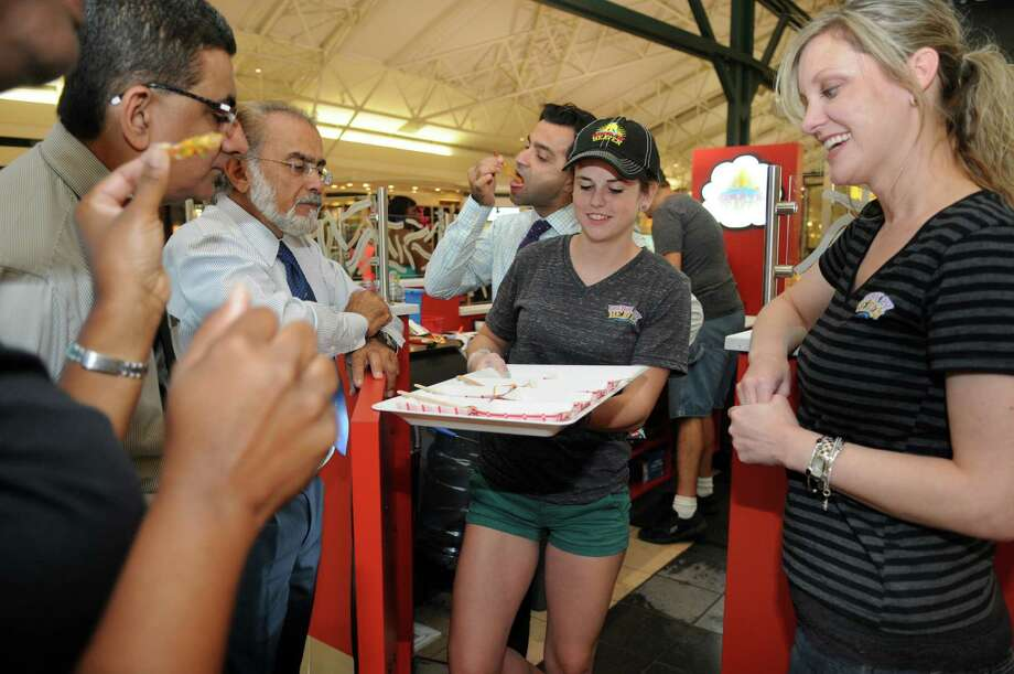 Hannah Staine, 16, offers samples to prospective franchisees under the direction of French Fry Heaven franchise owner Kim Davis. Photo: Jerry Baker, Freelance