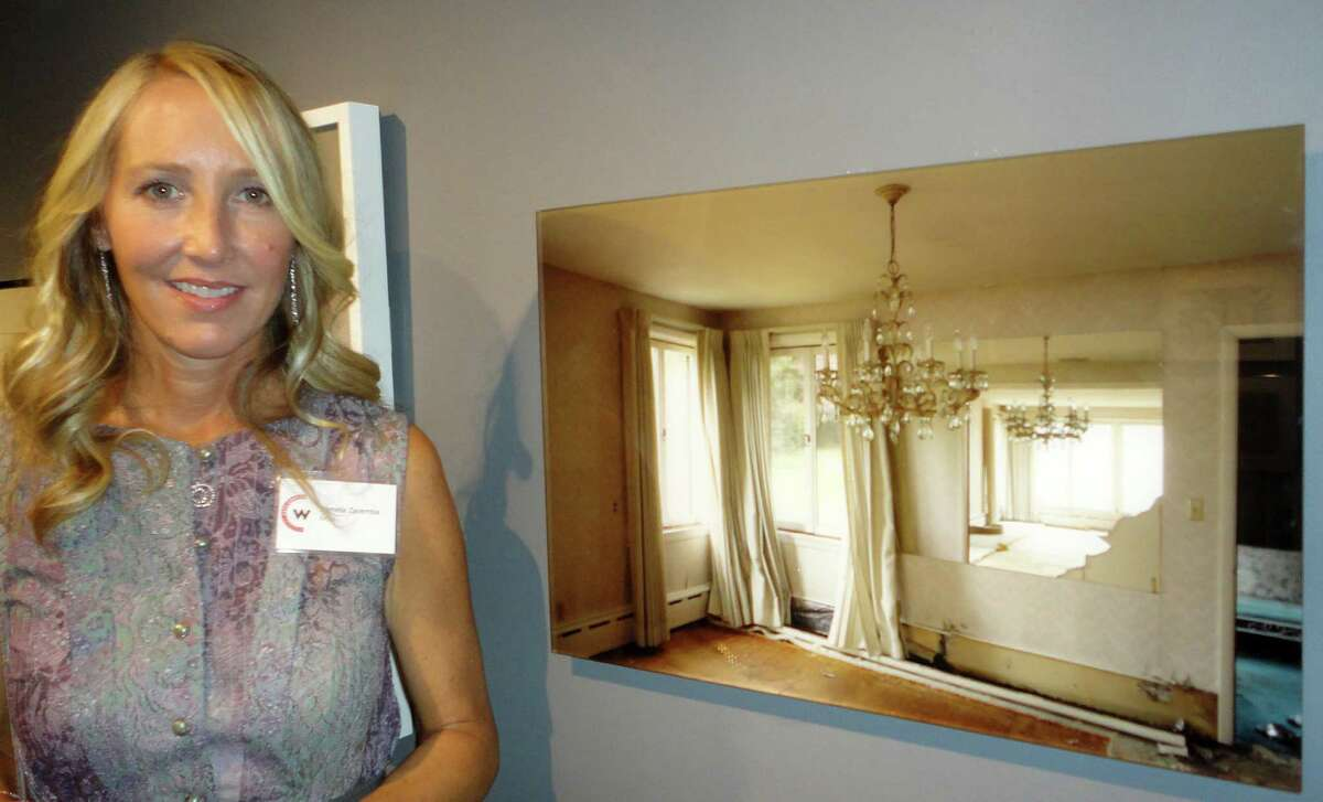 """Westport photographer Pamela Zaremba poses next to her juried entry, """"118 Hillside Rd,"""" in the Home Sweet Home exhibit at the Westport Arts Center."""