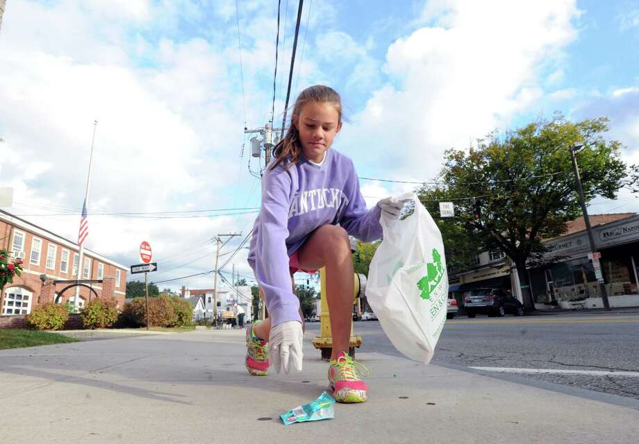 Greenwich resident, Eliza Farriss, 13, collects a discarded candy wrapper off the sidewalk on Sound Beach Avenue, Saturday, Sept. 21, 2013, during the Greenwich Clean & Green annual town-wide fall cleanup. Farriss was one of many volunteers taking part in the Green & Clean operation to beautify Greenwich. Photo: Bob Luckey / Greenwich Time