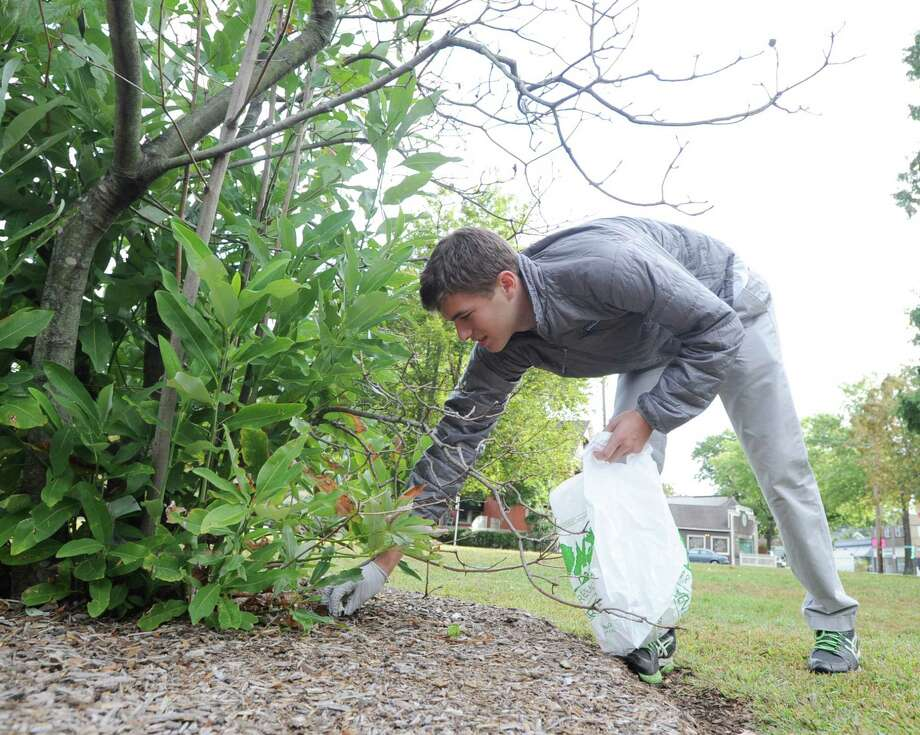 Volunteer, Scott D'Angelo, 17, of Greenwich, bags trash in a small park in Central Cos Cob, Saturday, Sept. 21, 2013, during the Greenwich Clean & Green annual town-wide fall cleanup. Photo: Bob Luckey / Greenwich Time
