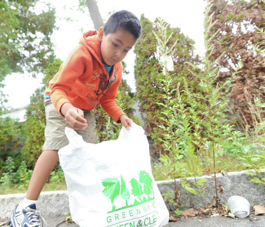David DaSilva, 8, of Greenwich, bags trash in the parking lot at the Cos Cob School, Saturday, Sept. 21, 2013, during the Greenwich Clean & Green annual town-wide fall cleanup. DaSilva, a third-grade student at the school, was one of many volunteers taking part in the Green & Clean effort to beautify Greenwich. Photo: Bob Luckey / Greenwich Time