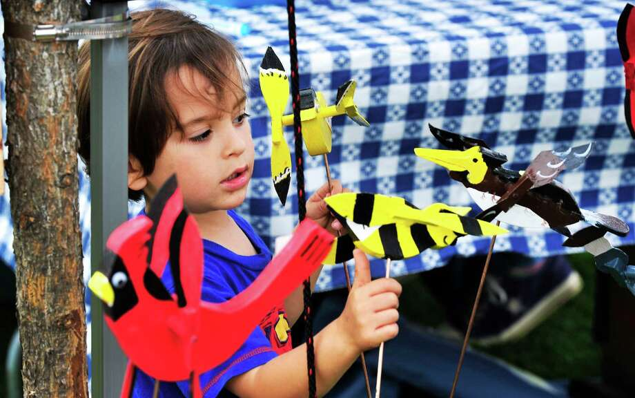 "Leo Tranquilli, 3, looks over wooden sculptures during the Newtown Arts Festival, an eight-day ""celebration of the arts,""  on the Fairfield Hills campus in Newtown, Conn. Saturday, Sept. 21, 2013. Photo: Michael Duffy / The News-Times"