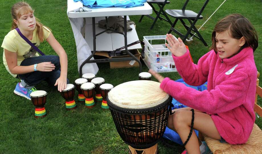 "Audrey Christensen, 11, left, and laire Buckley, 10, play dojembe drums during the Newtown Arts Festival, an eight-day ""celebration of the arts,""  on the Fairfield Hills campus in Newtown, Conn. Saturday, Sept. 21, 2013. Photo: Michael Duffy / The News-Times"