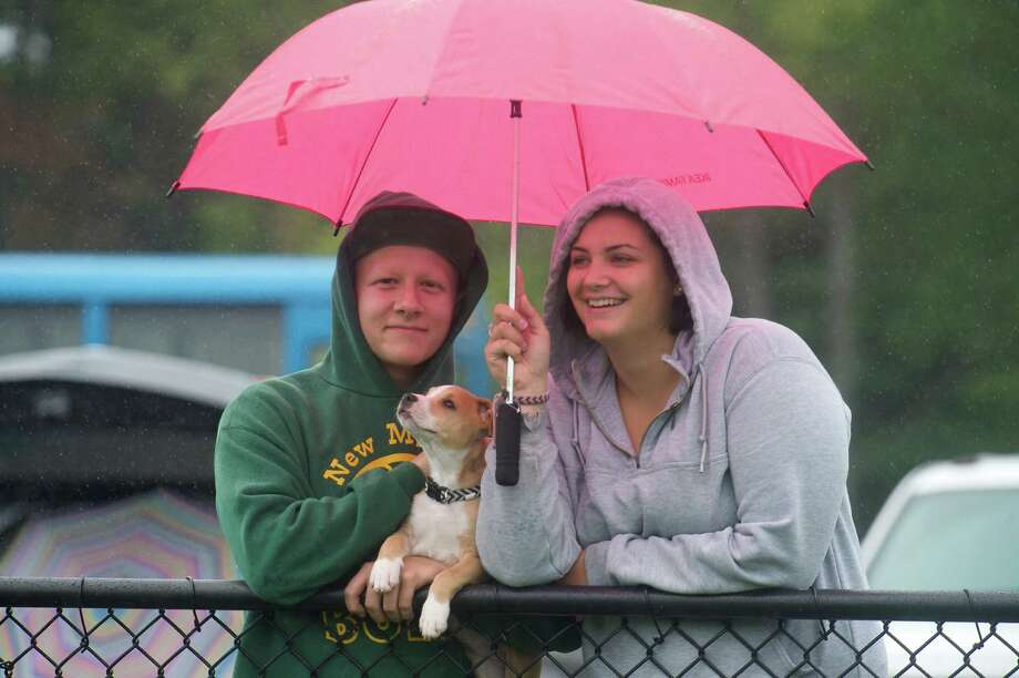 Spectators take cover under an umbrella during a downpour at the high school football game between Bullard-Havens and Abbott Tech at Rogers Park in Danbury, Conn, Saturday, September 21, 2013. Photo: H John Voorhees III