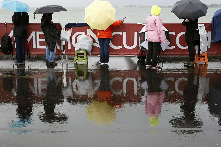 Fans brave rain in hopes of seeing America's Cup action, but the event was called off because of unfavorable southerly winds. Race 14 is now set for Sunday - as is Race 15, if needed. Photo: Michael Short, The Chronicle