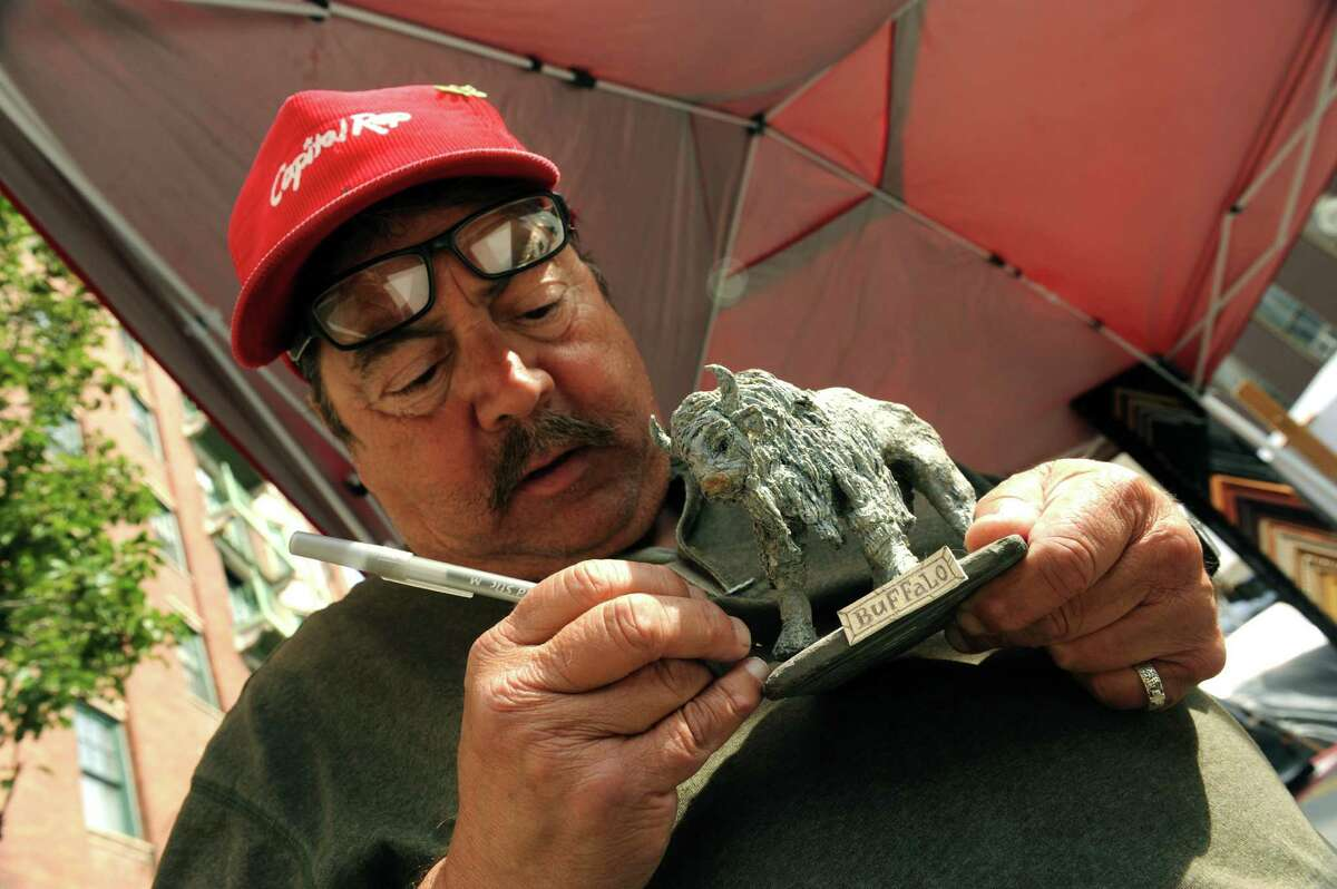 Artis Dennis Gervasio of Albany touches up one of his duct tape sculptures of a Buffalo on sale during the 2013 LarkFest on Saturday Sept. 21, 2013 in Albany, N.Y. (Michael P. Farrell/Times Union)