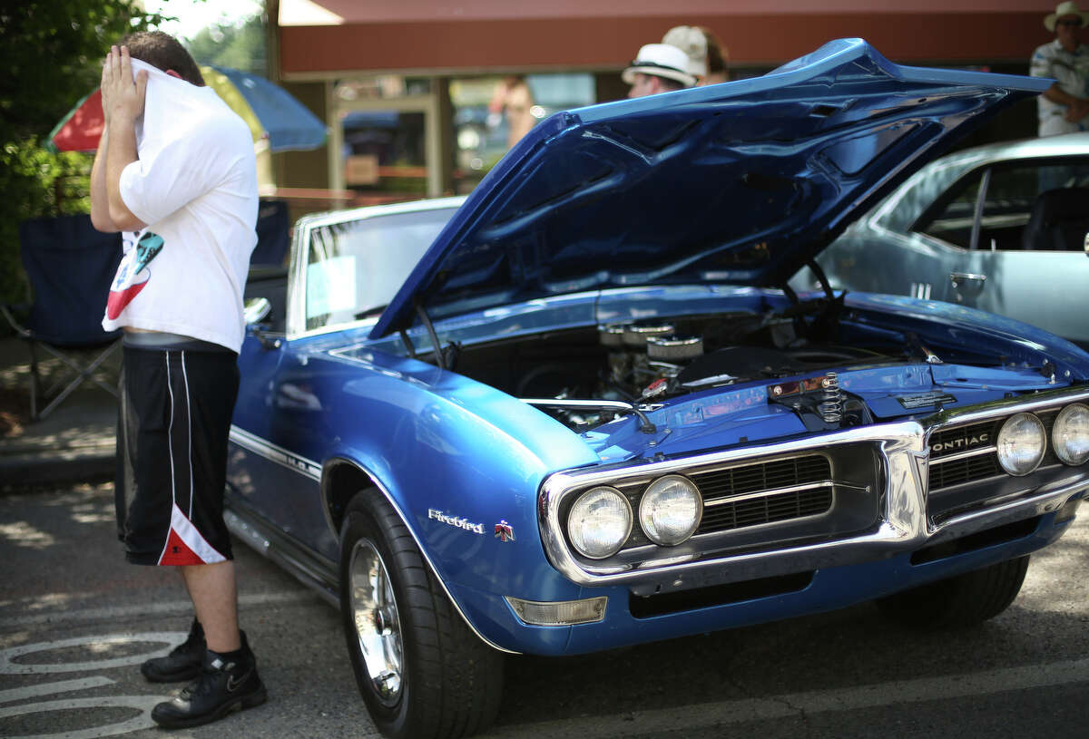 A man wipes sweat from his head as temperatures hover in the mid-80s during the Greenwood Car Show. The annual show is the largest single-day car show in the state.