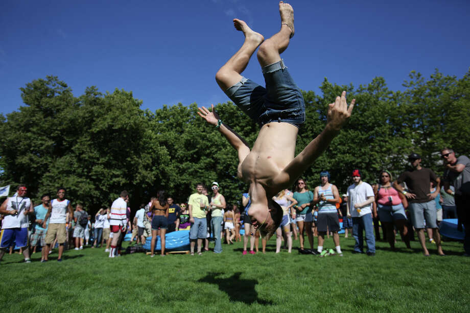 A participant does a flip during an attempt to set a Guinness World Record for the largest water balloon fight Aug. 17. The group of 4,256 human water balloon cannons were unable to smash the previous record of 8,957. Photo: JOSHUA TRUJILLO, SEATTLEPI.COM / SEATTLEPI.COM