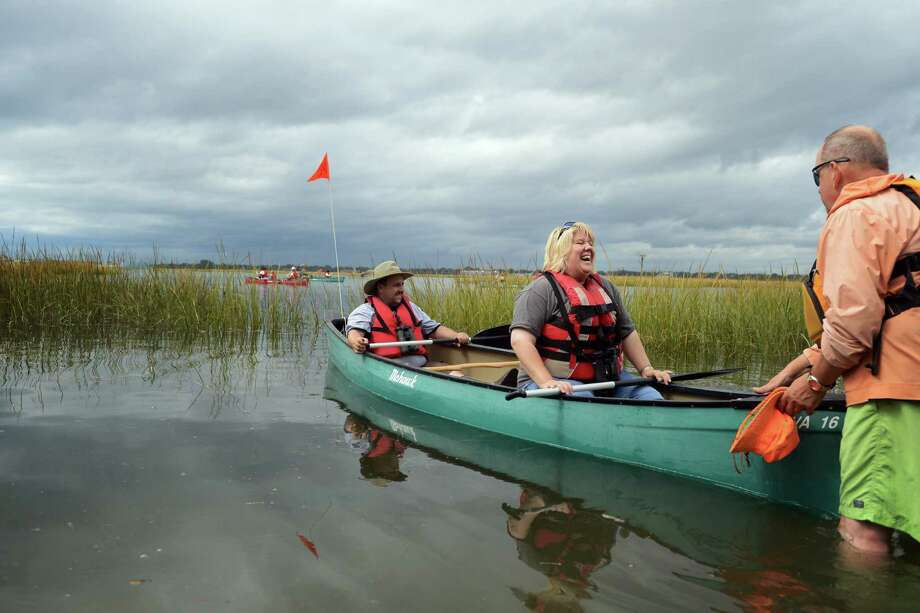 Dan and Karen Mercurio, of Meriden, head out into the marsh with a push from volunteer Bob Miko, of Stratford, Saturday, Sept. 21, 2013 during the CT Audubon Society's Family Canoe Program through the Charles E. Wheeler Salt Marsh.   Tours continue on Sunday, Sept. 22 from 12:15 p.m. âÄì 2:45 p.m., and on Sunday, October 6 and Sunday, October 20, at 11:15 a.m. Photo: Autumn Driscoll / Connecticut Post