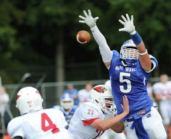 At left, Greenwich quarterback Jose Melo (# 4) throws the ball as Rock Stewart (# 5) of Darien bats down his pass attempt while being blocked by Kevin Woodring (# 71) of Greenwich during the high school football game between Darien High School and Greenwich High School at Darien, Saturday, Sept. 21, 2013. Darien defeated Greenwich,42-21. Photo: Bob Luckey / Greenwich Time