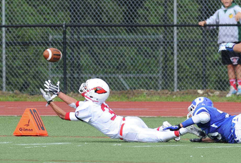 At left, Austin Longi (# 3) of Greenwich stretches-out on an attempted reception during the high school football game between Darien High School and Greenwich High School at Darien, Saturday, Sept. 21, 2013. Although Longi was unable to make the catch, pass interference was called against Darien. Darien defeated Greenwich,42-21. Photo: Bob Luckey / Greenwich Time