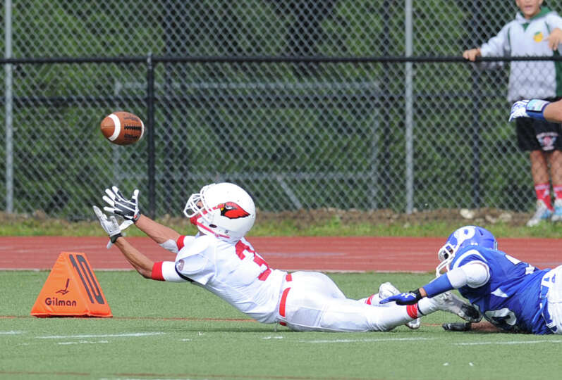At left, Austin Longi (# 3) of Greenwich stretches-out on an attempted reception during the high sch