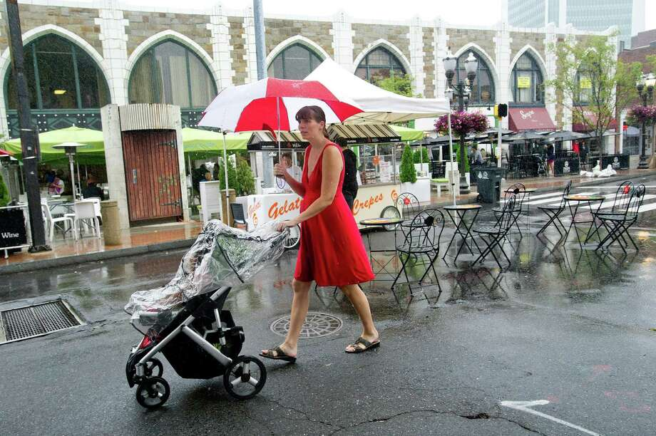 Jen Parsons holds an umbrella as she walks down Bedford streen in the rain with her daughter, Saelle, 2, in the stroller during Arts & Crafts on Bedford in Stamford, Conn., on Saturday, Sept. 21, 2013. Photo: Lindsay Perry / Stamford Advocate