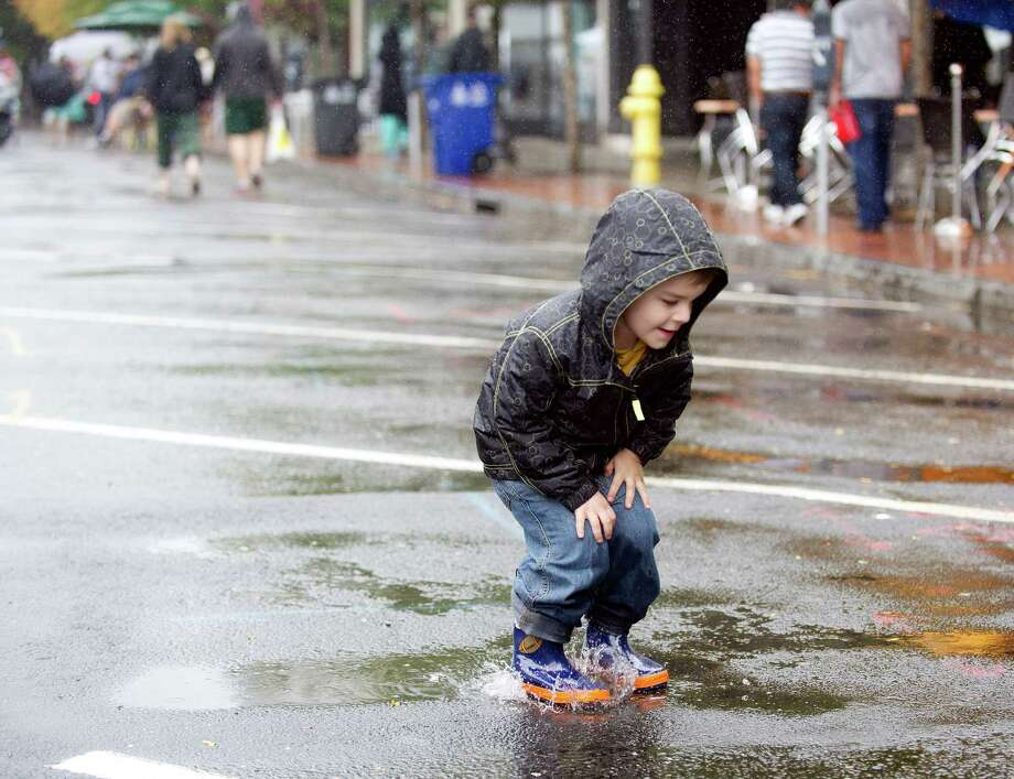 Tristan Kozlowski, 3, jumps in a puddle during Arts & Crafts on Bedford in Stamford, Conn., on Saturday, Sept. 21, 2013. Photo: Lindsay Perry / Stamford Advocate