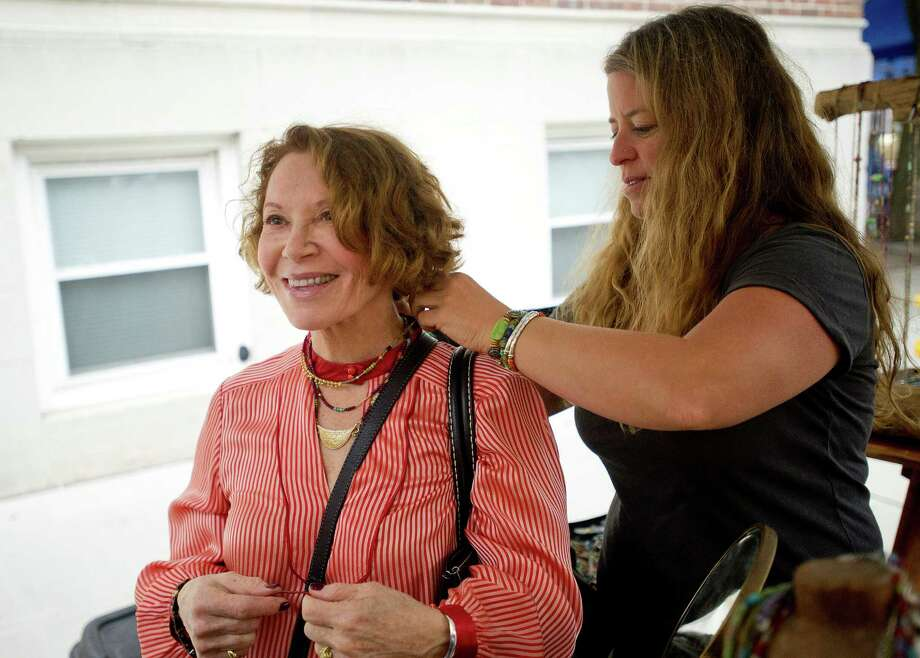 Jill Scholsohn of Riverstone Jewelry puts a necklace on Janice Restler during Arts & Crafts on Bedford in Stamford, Conn., on Saturday, Sept. 21, 2013. Photo: Lindsay Perry / Stamford Advocate