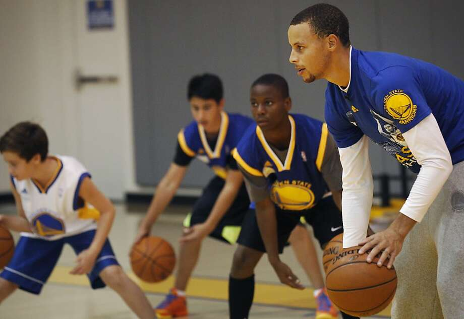 "Steph Curry (right) leads a dribbling drill during Friday's ""Splash Brothers Fantasy Basketball Clinic"" at the Warriors' Oakland practice facility. Photo: Leah Millis, The Chronicle"