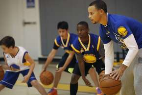 Steph Curry, right, leads a dribbling drill during a a father and son shooting and passing clinic September 20, 2013 at the Warriors practice facility, on the top floor of the Oakland Convention Center in Oakland, Calif.