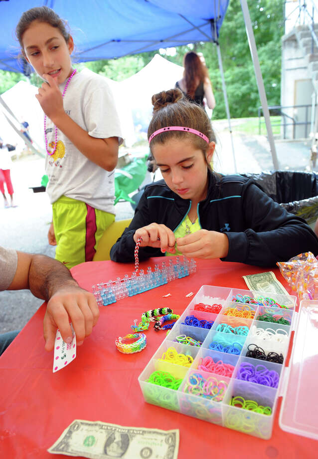 Jackie Matthews, 12, creates rainbow loom bracelets for the other kids at the annual Middle Eastern food festival at St. Nicholas Antiochian Orthodox Church in Bridgeport, Conn. on Saturday September 21, 2013. All the money Matthews raises by selling the bracelets will go to the church. Photo: Christian Abraham / Connecticut Post