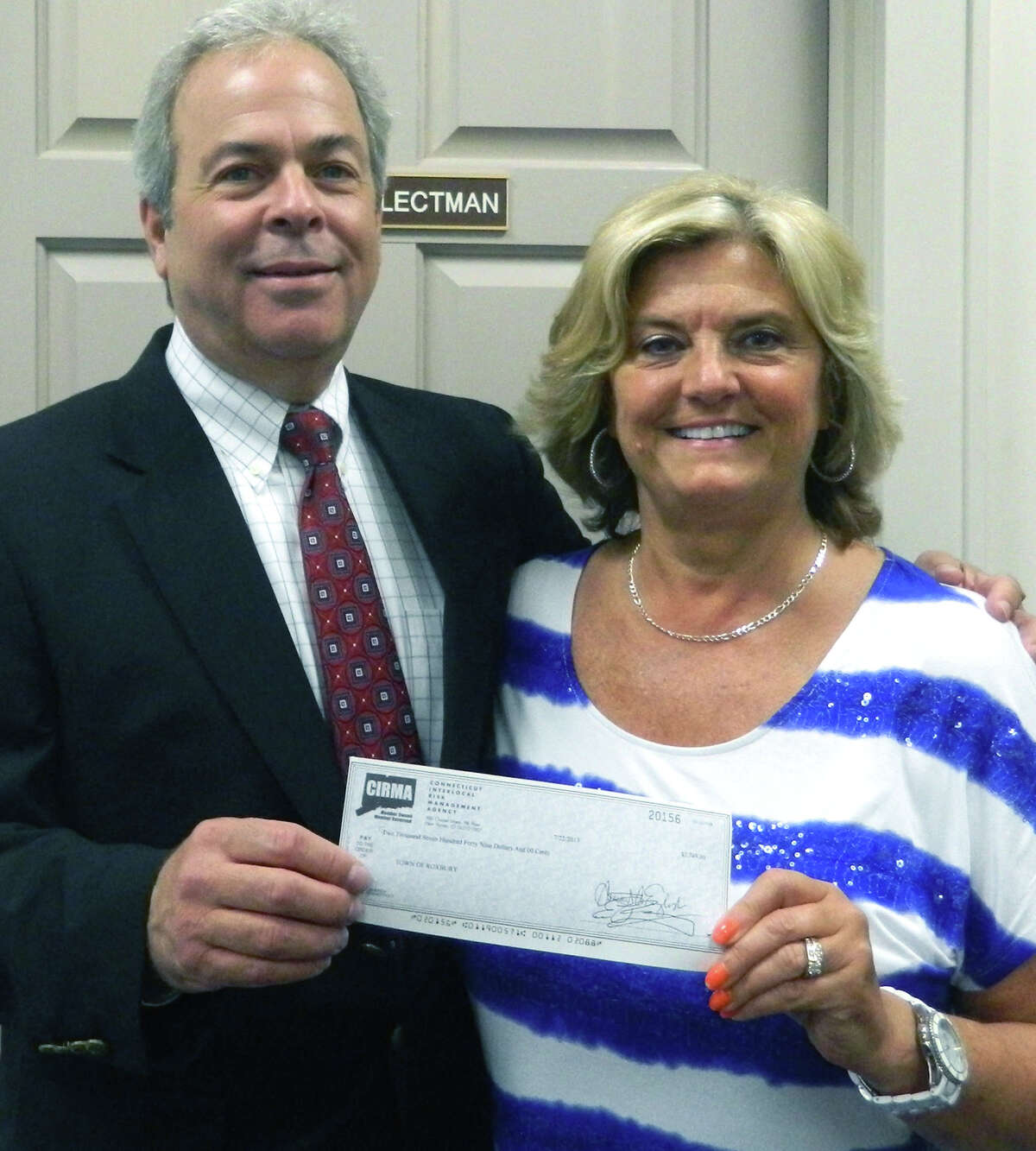 Steven Bixler, vice president for underwriting, marketing and member relations of the Connecticut Interlocal Risk Management Agency, presents a check for $2,749, the town's pro-rated share of CIRMAís $3 million membersí equity distribution for 2013,.to Roxbury First Selectman Barbara Henry. August 2013 Courtesy of the Town of Roxbury