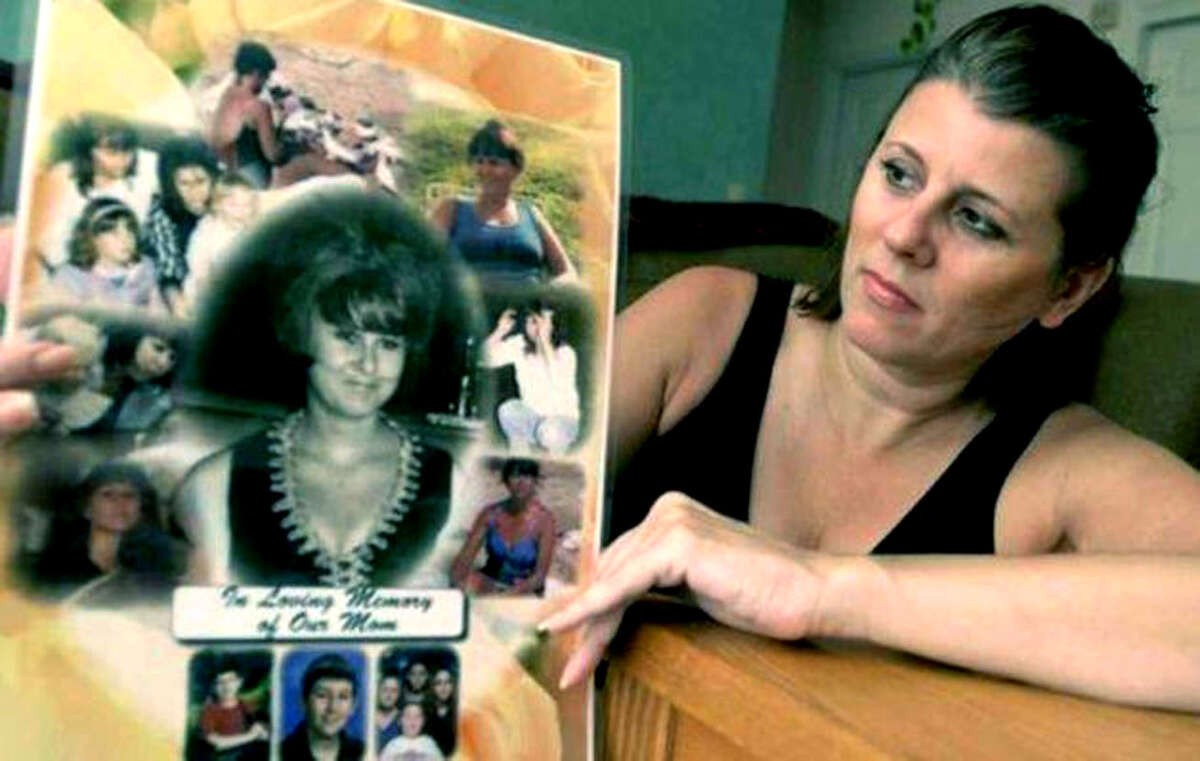 Sherrie Passaro of Danbury holds a poster of photographs in memory of her mother, Mary Badaracco, who disappeared from her Sherman home years ago.