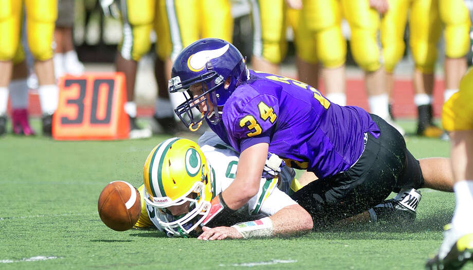 Trinity Catholic's Connor Amann loses control of the ball as he is tackled by Westhill's Joe Schlessinger during Saturday's football game at Westhill High School on Sept. 21, 2013. Photo: Lindsay Perry / Stamford Advocate
