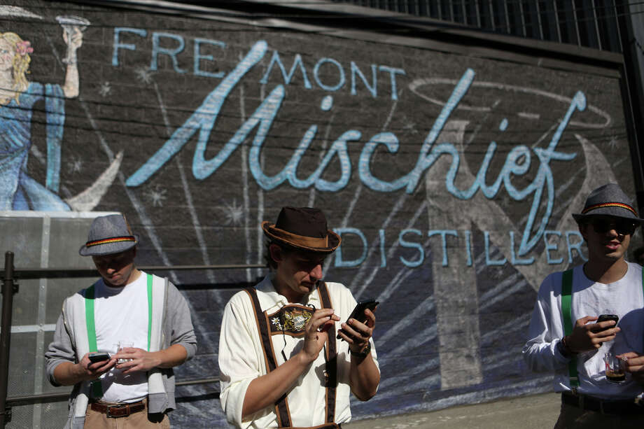 From left, Andrew Fabrizius, Stephen Elser and Matt Sunday check their smart phones during the annual Fremont Oktoberfest on Saturday, Sept. 21, 2013. Photo: JOSHUA TRUJILLO, SEATTLEPI.COM / SEATTLEPI.COM