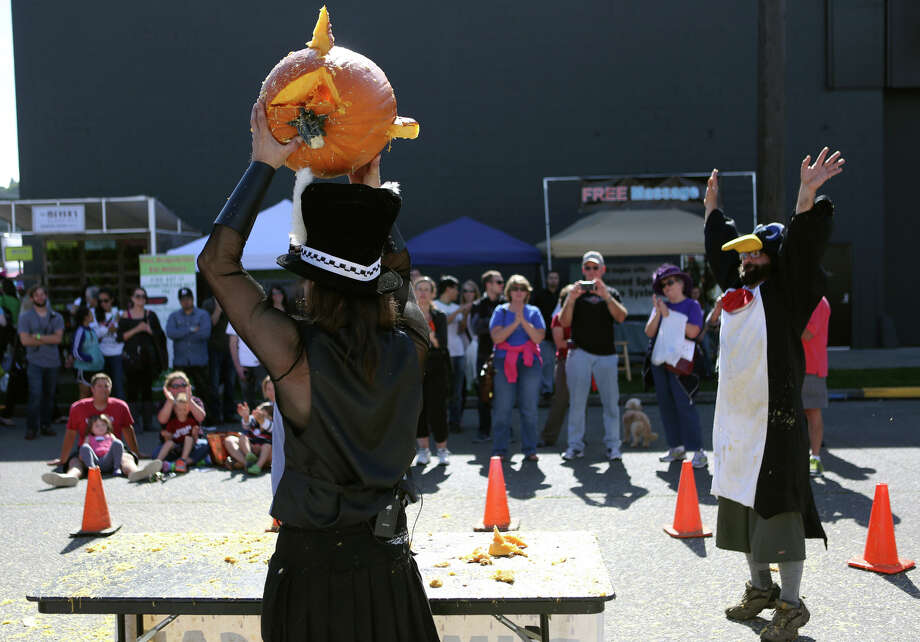 David Roman hoists the pumpkin creation from Rob Beck, aka Chilly Willis, during the Texas Chainsaw Pumpkin Carving Contest at the annual Fremont Oktoberfest on Saturday, Sept. 21, 2013. Photo: JOSHUA TRUJILLO, SEATTLEPI.COM / SEATTLEPI.COM