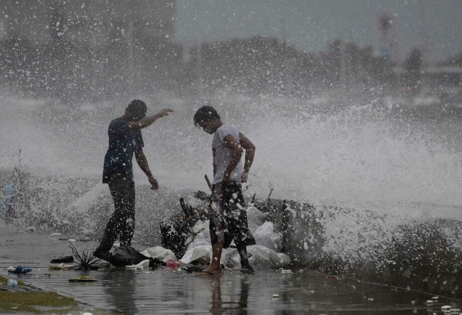Filipino workers are hit by splashes from a strong wave driven by Typhoon Usagi as it strikes the wall along a bayside promenade in Manila. Photo: Aaron Favila / Associated Press