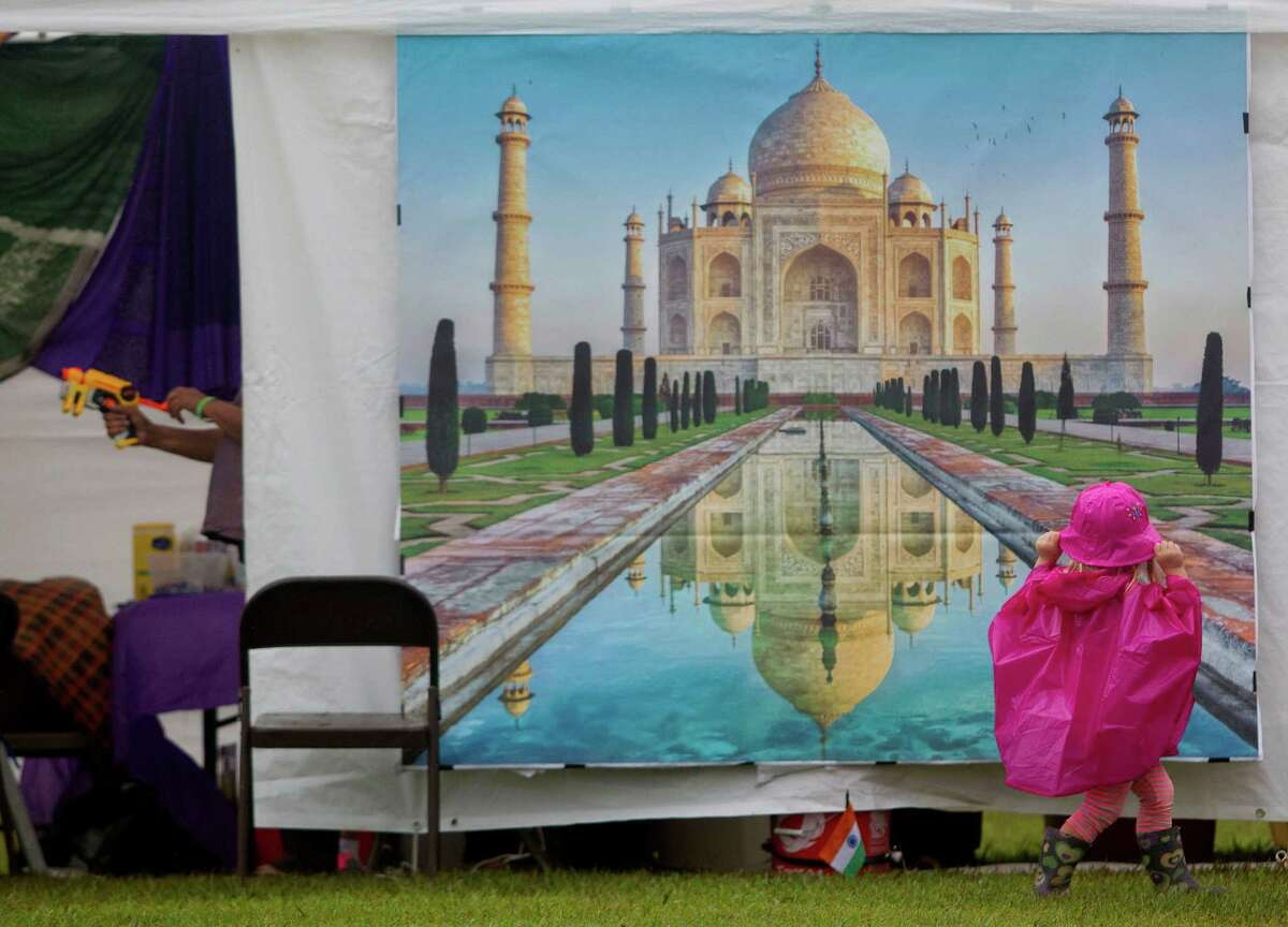 Lillian Matherne, 3, glances at a picture of the Taj Mahal on the Sharon Fellowship Church tent at the Pearland International Festival in Independence Park Saturday, Sept. 21, 2013, in Pearland.