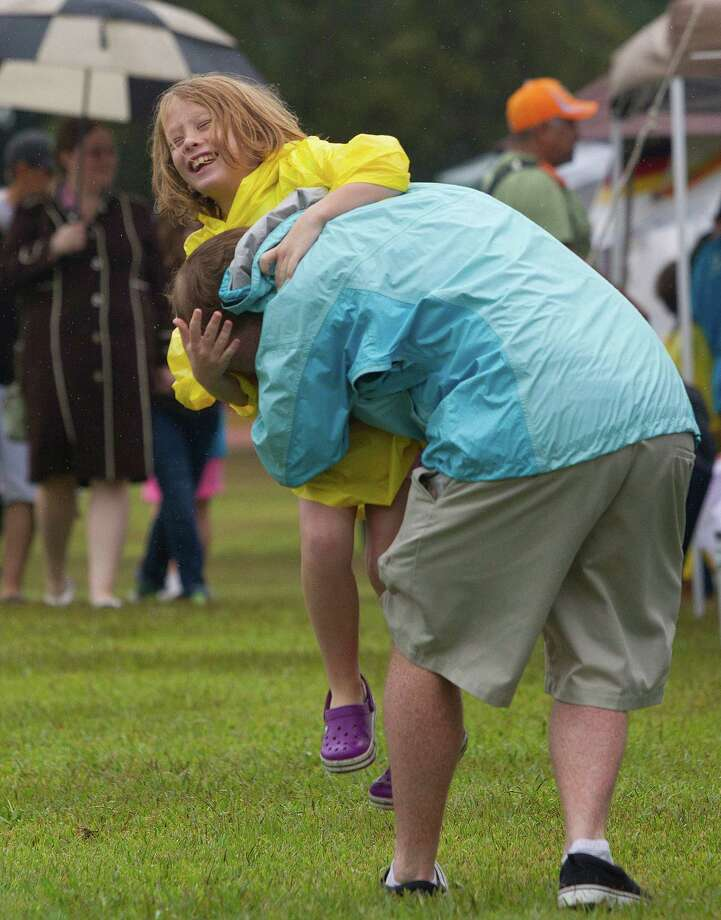 Ella Daley, 8, is picked up by her father Ben Daley at the Pearland International Festival in Independence Park Saturday, Sept. 21, 2013, in Pearland. Photo: Johnny Hanson, Houston Chronicle / Houston Chronicle