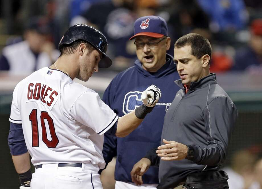 Terry Francona, center, and trainer Lonnie Soloff check on Yan Gomes (10) after he was hit by a pitch. Photo: Mark Duncan, Associated Press