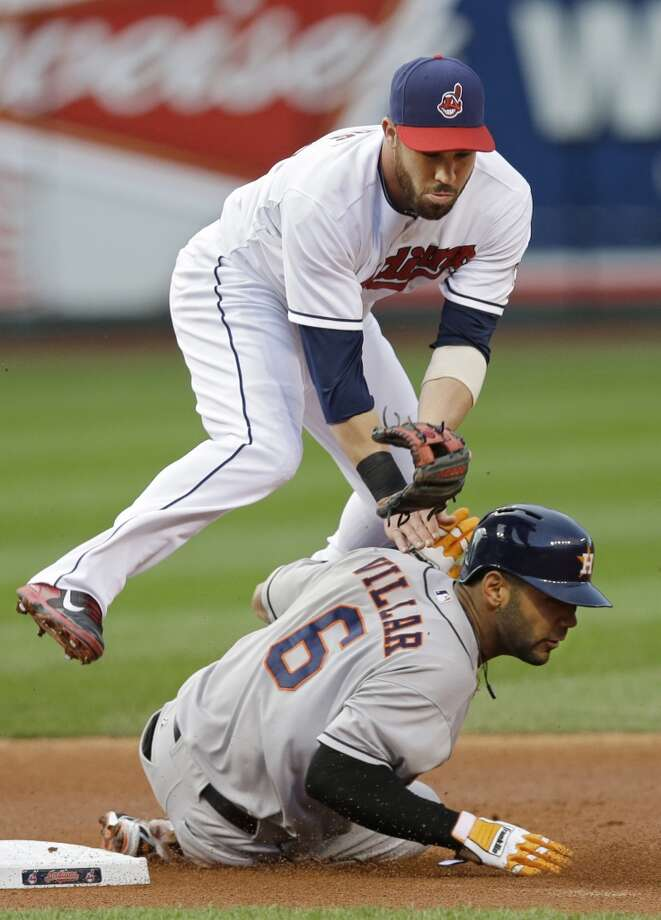 Indians second baseman Jason Kipnis tumbles over Jonathan Villar (6) after throwing to first to complete a double play on Jose Altuve. Photo: Mark Duncan, Associated Press
