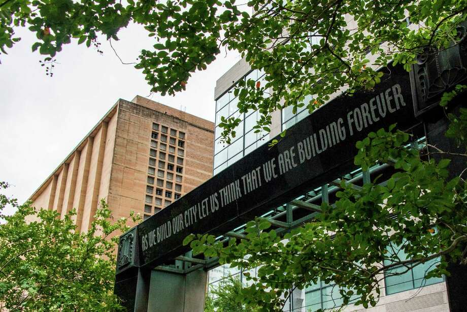 "The inscription reading ""As we build our city let us think that we are building forever"" is seen on the ""The Water Screen"" sculpture by Michael Davis that overlooks the fountain on Main Steet Square near the former Macy's department store building, left, in downtown Houston. Photo: Smiley N. Pool, Houston Chronicle / © 2013  Houston Chronicle"