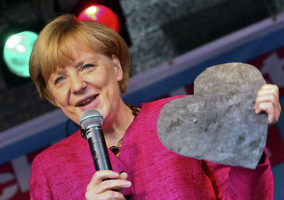 German Chancellor Angela Merkel holds a heart-shaped piece of slate she was given during an election campaign event of the Christian Democratic Union party in Stralsund a day before general elections. Photo: Jens Buettner / Getty Images